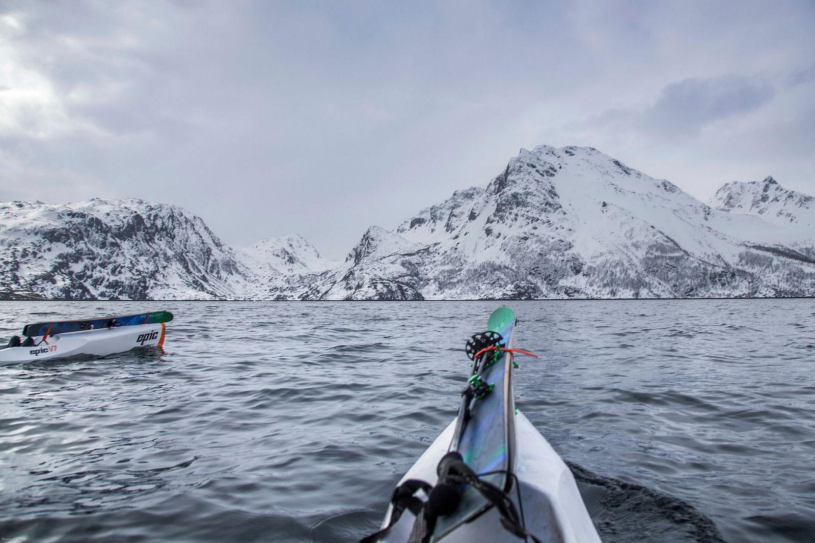 Fjellet Joahkonjárga ligger foran skituppene på kajakkene som krysser fjorden. Det 904 meter høye fjellet skal bestiges på dagens skitur.