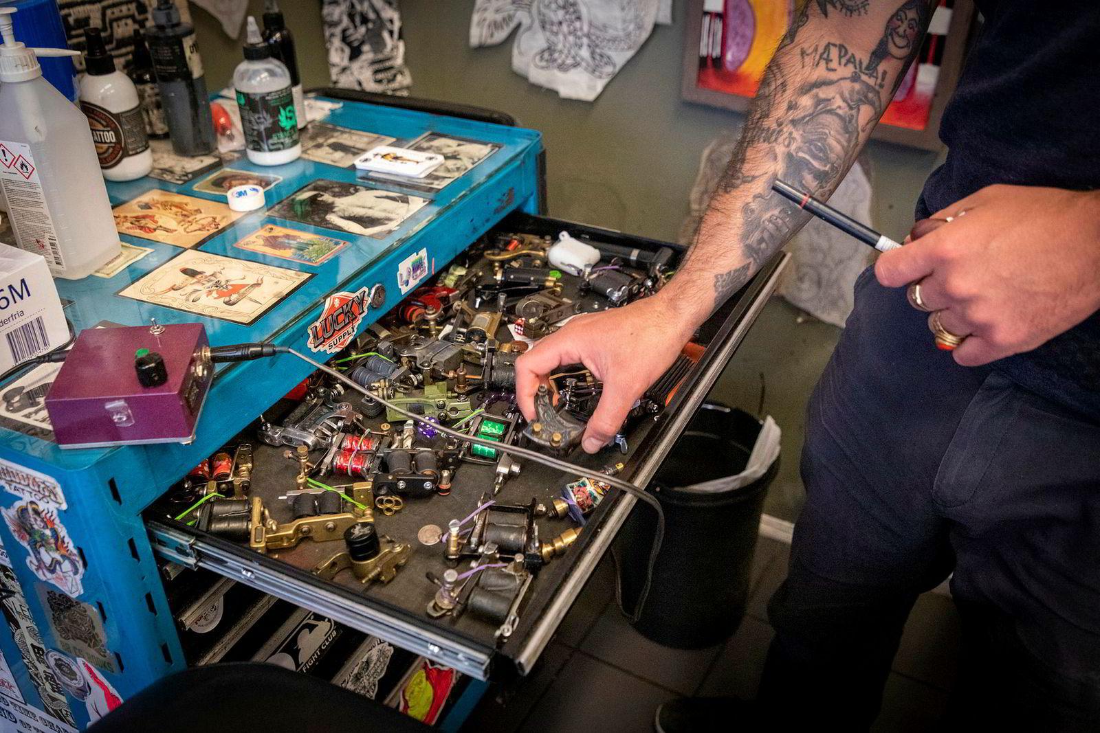 Dinson Purcell venter på at kundene skal komme tilbake til hans tatoveringsstudio sentralt i Oslo. I mellomtiden rydder han i utstyrsskuffen.