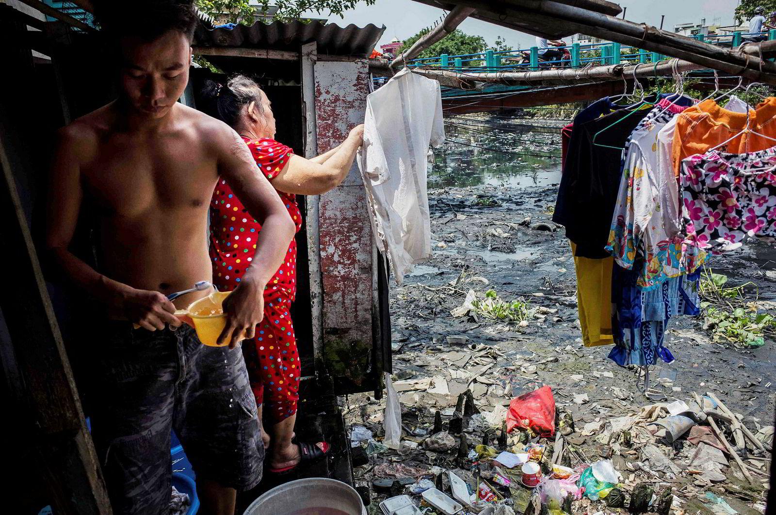 En kvinne henger opp klær utenfor et av husene ved kanalen. Elvebredden utenfor huset er sterkt preget av plast og avfall.
