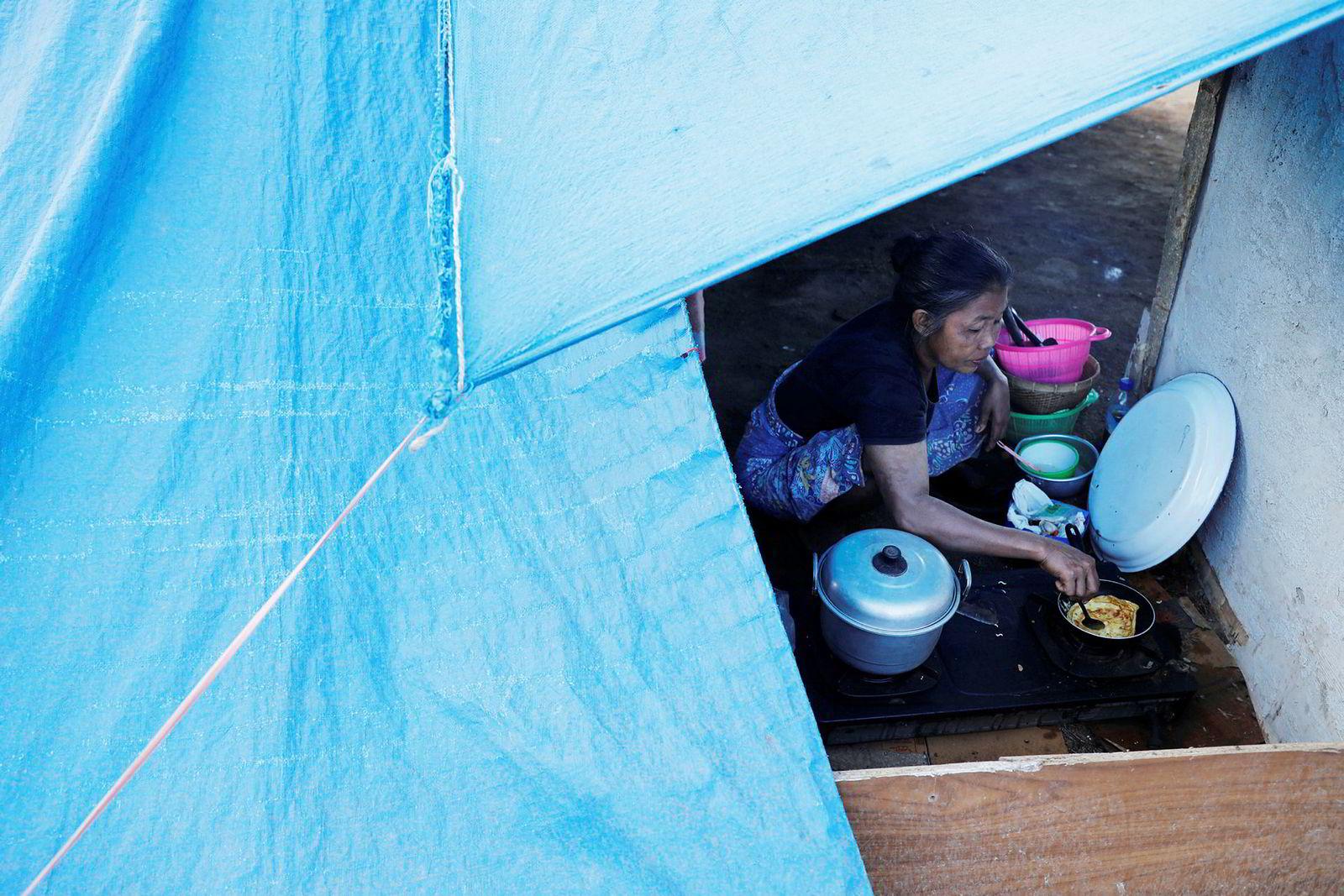 En kvinne lager seg frokost i en av flyktningleirene som er satt opp på øya Lombok etter jordskjelvene.