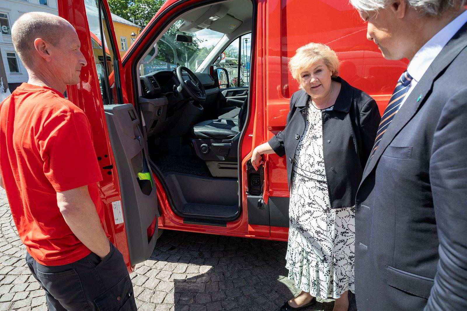 Statsminister Erna Solberg har funnet ladeluken til Kjell Arne Haugens elektriske postbil. Miljøvernminister Ola Elvestuen til høyre.