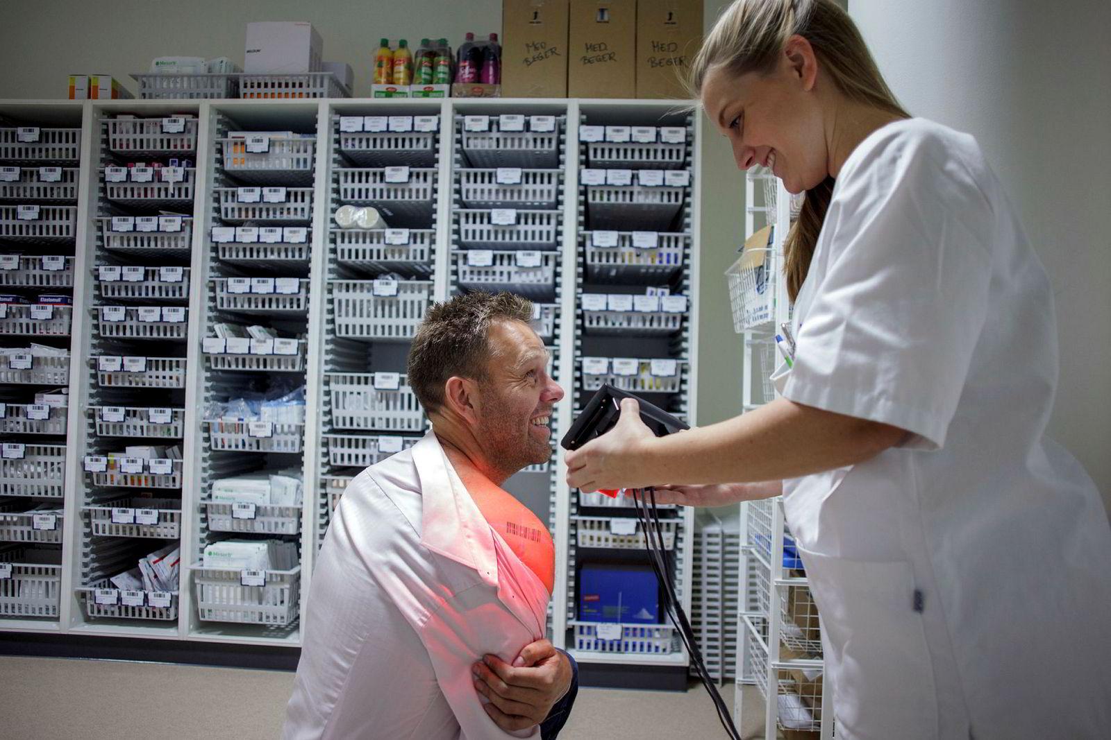 Daglig leder i it-selskapet Ascan, Bjørn Gregersen viser frem sin tatoverte strekkode for sykepleier Stine Sæther i Tønsbergregionen Legevakt.