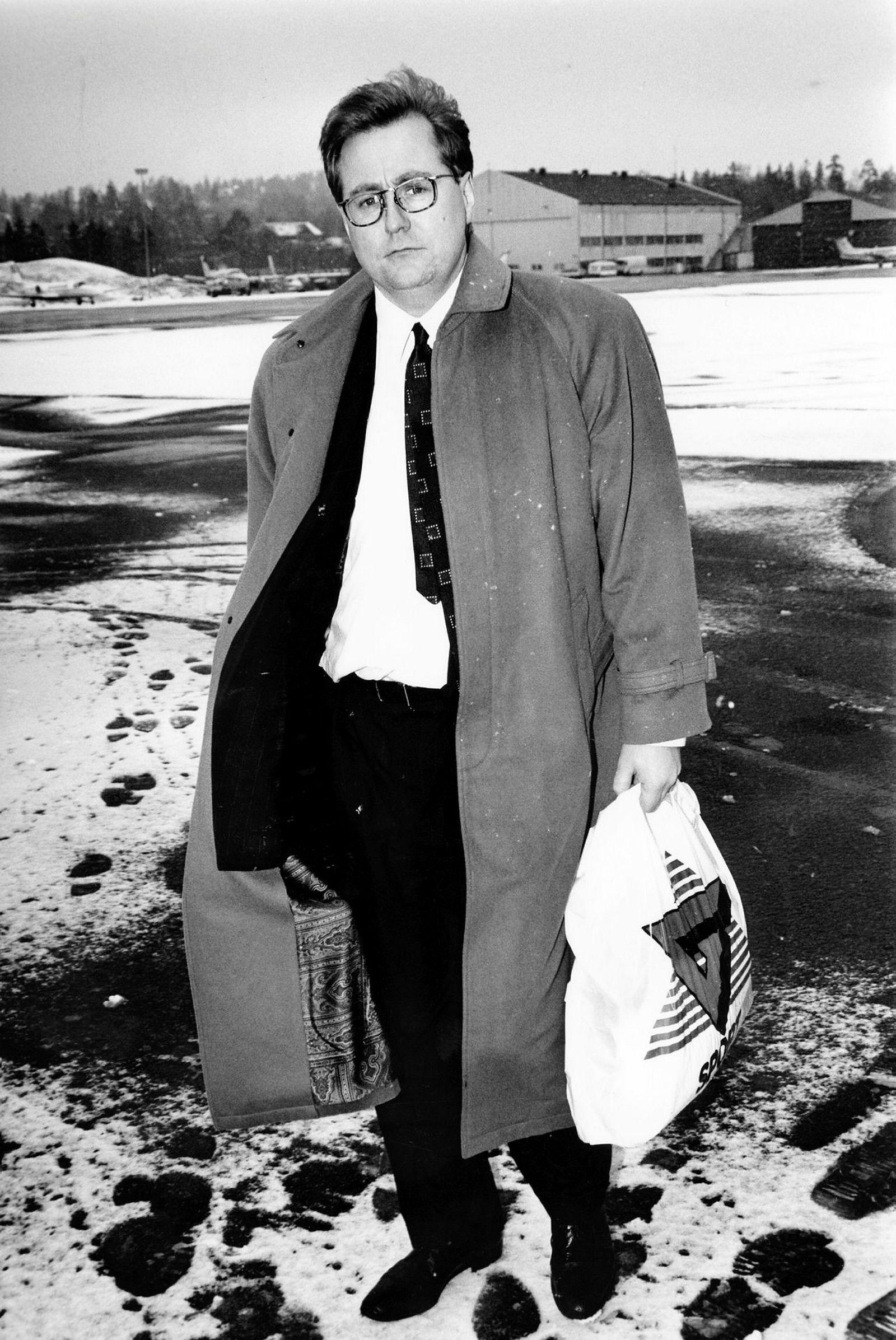 Kjell Inge Røkke, her avbildet i mars 1994, i lang frakk og dress, med en pose fra sportskonsernet Gresvig som han eide og drev med Bjørn Rune Gjelsten på den tiden.