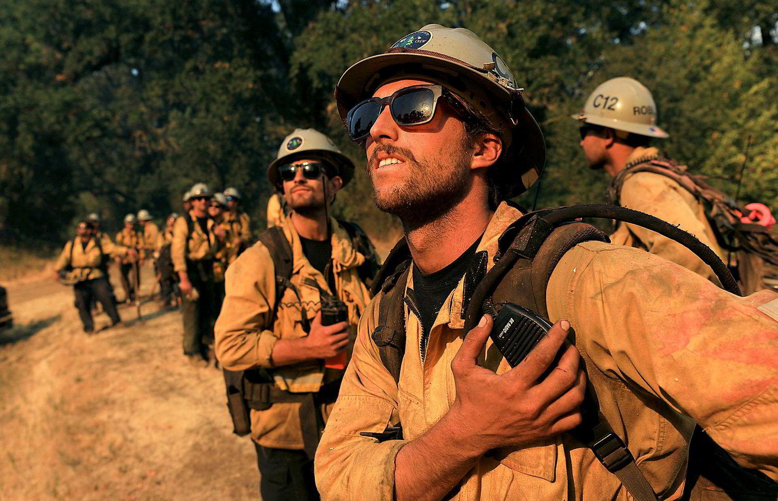 Brannmannen Caleb Amico og kollegene overværer et helikopter som driver slukningsarbeid i Scotts Valley i California.