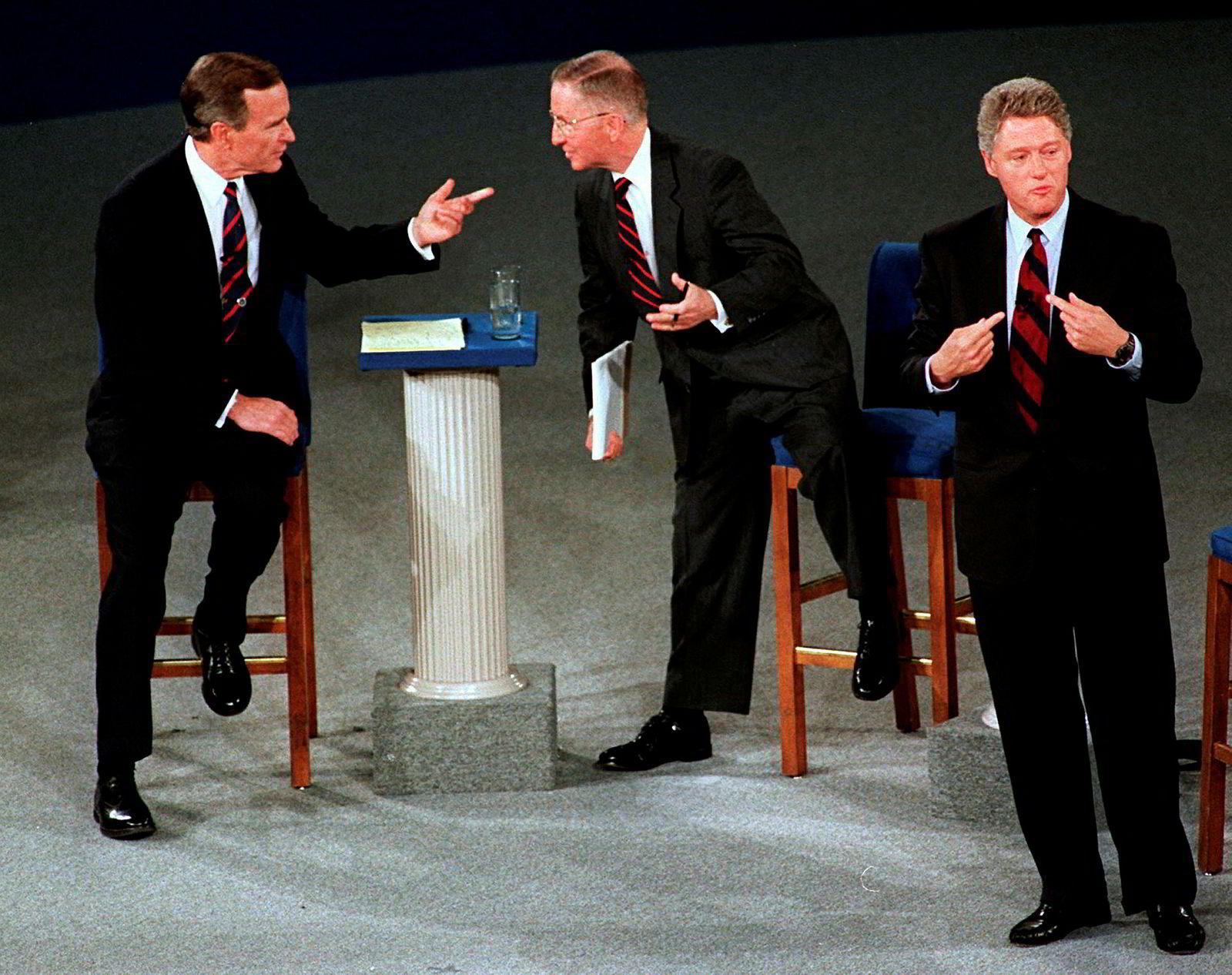 F.v. President George H. W. Bush prater med den uavhengige presidentkandidaten Ross Perot, mens Demokratenes presidentkandidat, Bill Clinton, er henvendt mot publikum i en kandidatdebatt i oktober 1992.