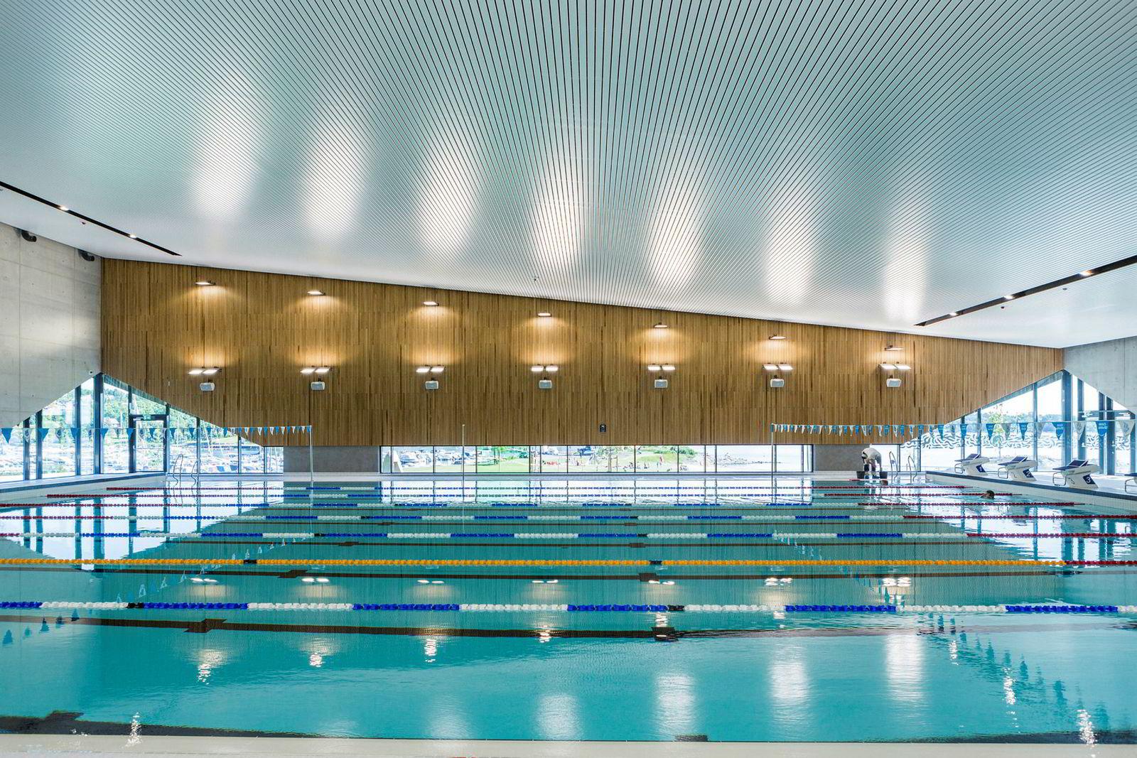 Dekket av solceller og solfangere, bruker Holmen Svømmehall 45 prosent mindre energi enn en tilsvarende hall. Under bakken ligger geobrønner som fylles opp om sommeren og tappes om vinteren. Alt monitoreres og analyseres, slik at så lite energi som mulig går til spille.