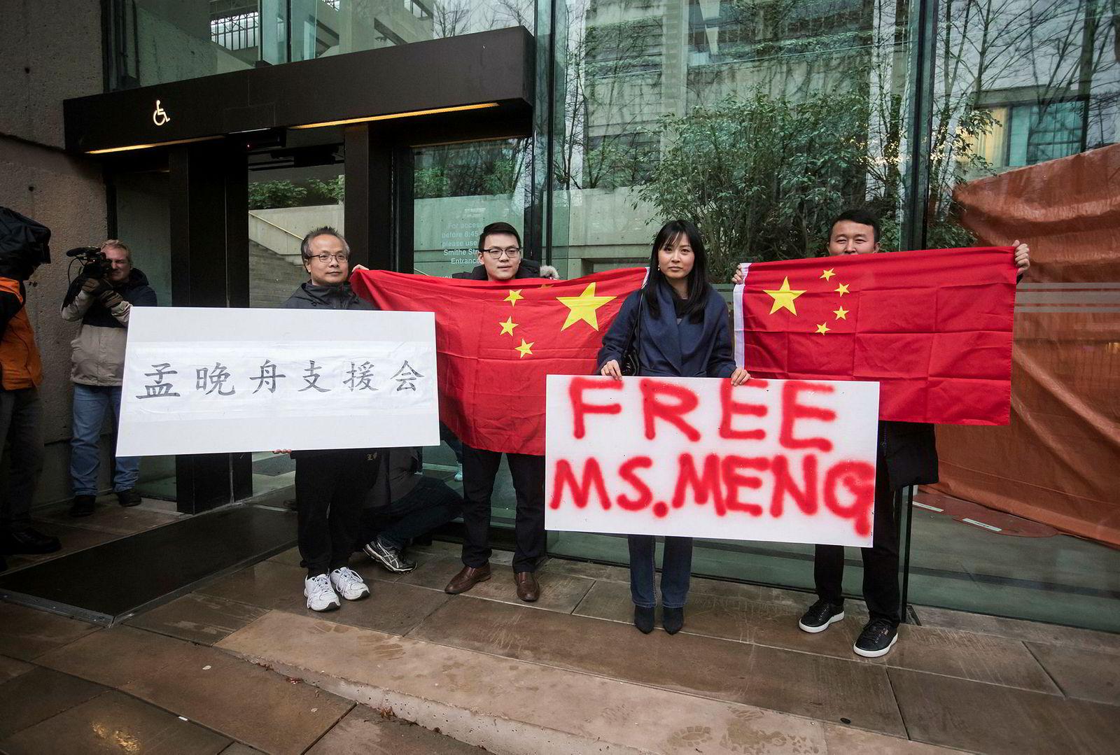 Tilhengere av Meng Wanzhou, finansdirektør i Huawei Technologies, holder plakater og kinesiske flagg utenfor British Columbia Supreme Court, Vancouver under en høring for Meng Wanzhou i desember.