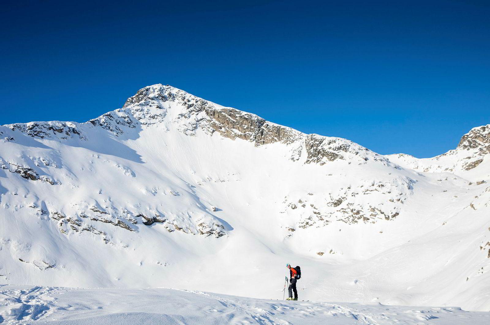 Solen står høyt over Skitntind (i bakgrunnen) og fjellene på Kvaløya utenfor Tromsø. Mildvær med påfølgende kulde har preget snøen høyt til fjells denne vinteren.