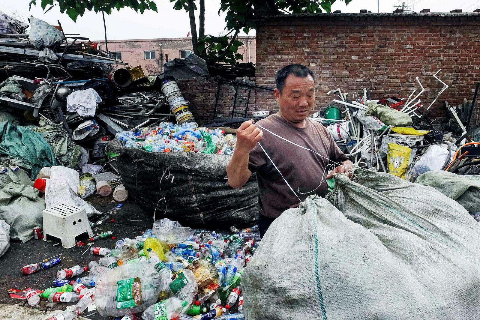 I utkanten av Beijing samler en mann plastflasker på et plastavfallsanlegg.