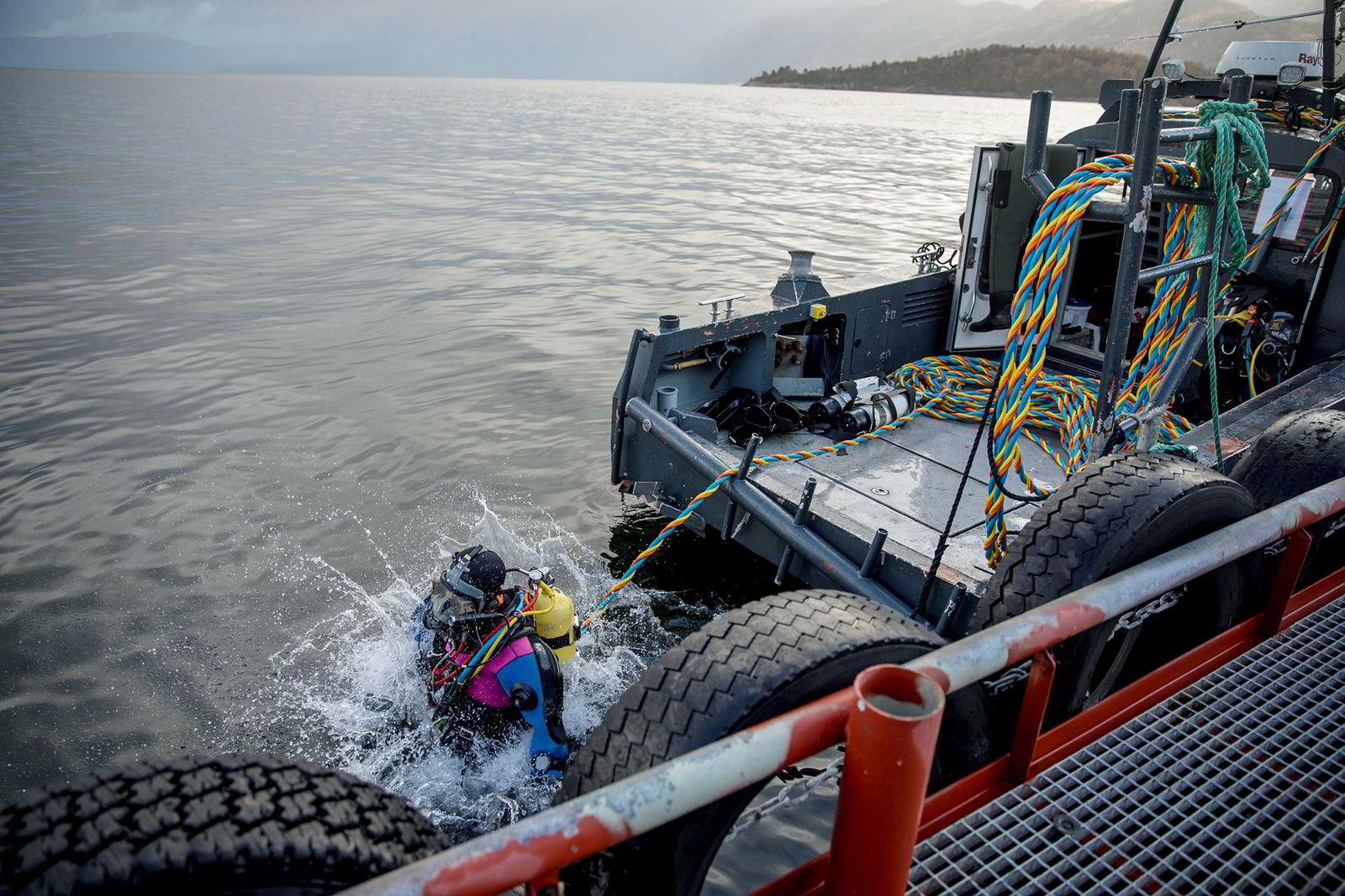 Oppdrettsdykker Ragnhild Jesica Bjella hopper uti sjøen for å sjekke notveggen ved anlegget på Hågardsneset.