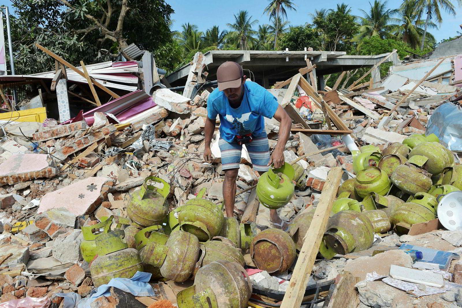 En mann henter beholdere med gass til matlaging fra ruinene til svigerbroren sin i Pemenang i Indonesia. Dødstallet fra et jordskjelv med en styrke på 6.9 er fremdeles usikkert. Ulike etater oppgir tall mellom 200 og 400.