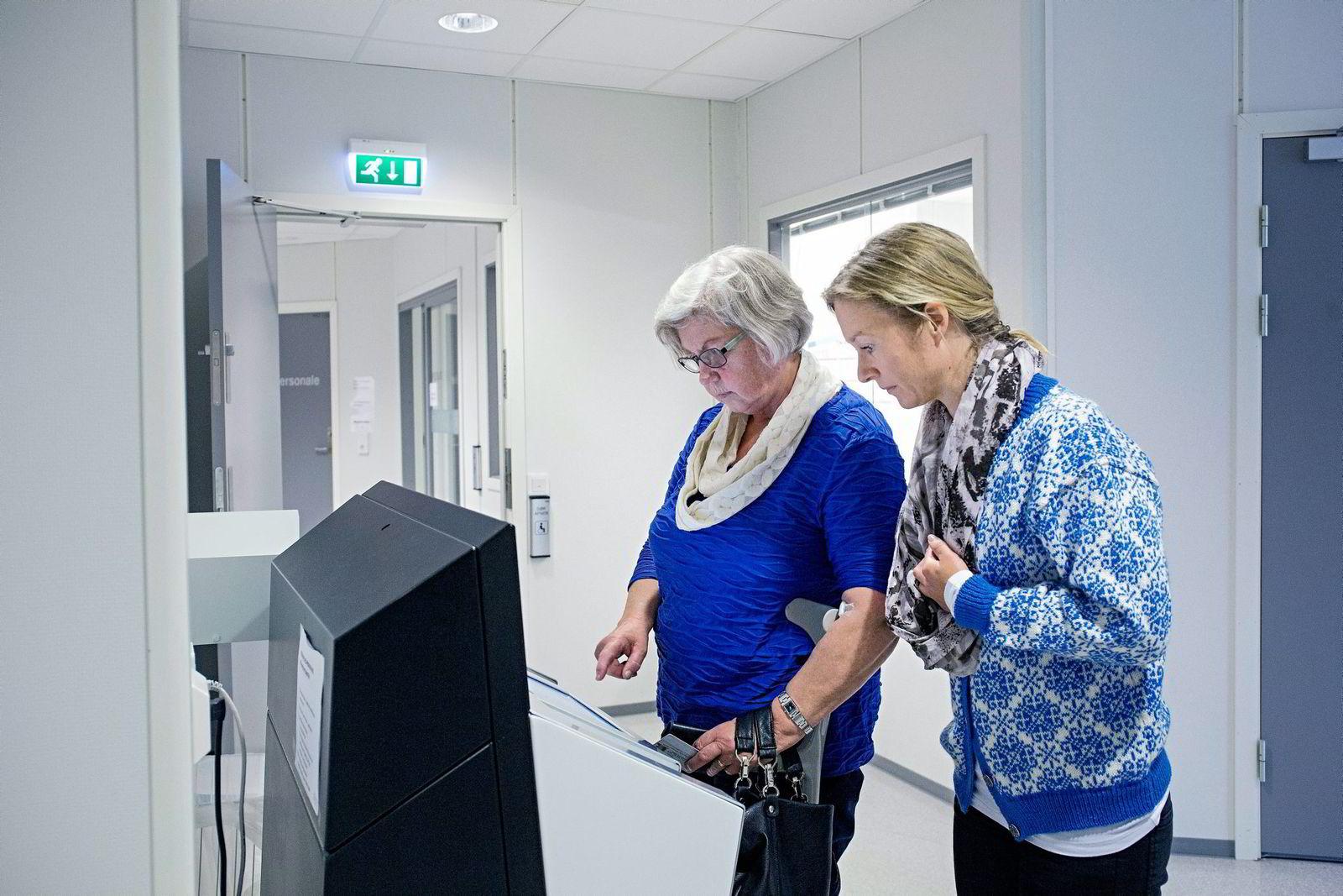 Randi Margrethe fra Sandane skal betale på Melin-terminalen på legekontoret i Sandane, og får hjelp av Melin Medical-sjef Ingvill Hestenes.