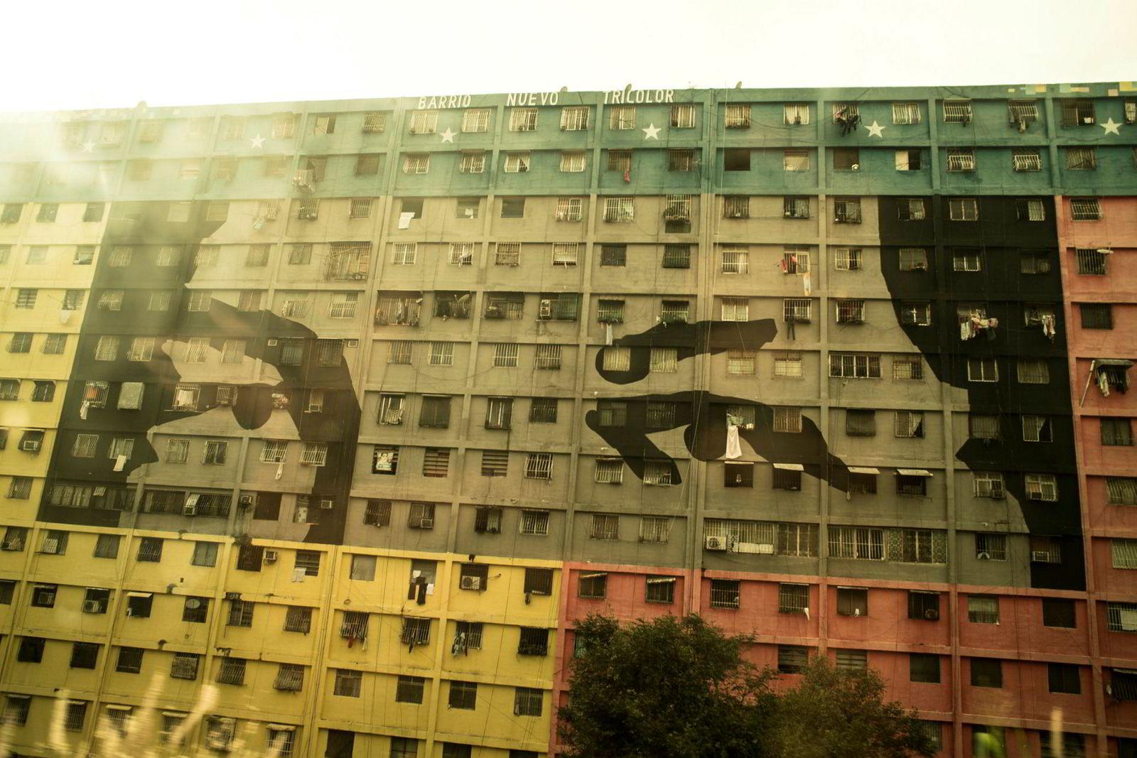 Den avdøde presidenten Hugo Chávez på fasaden til en boligblokk i en slum i Caracas. Regimet mener det allestedsværende blikket skal minne folket om deres ideologiske forpliktelser.