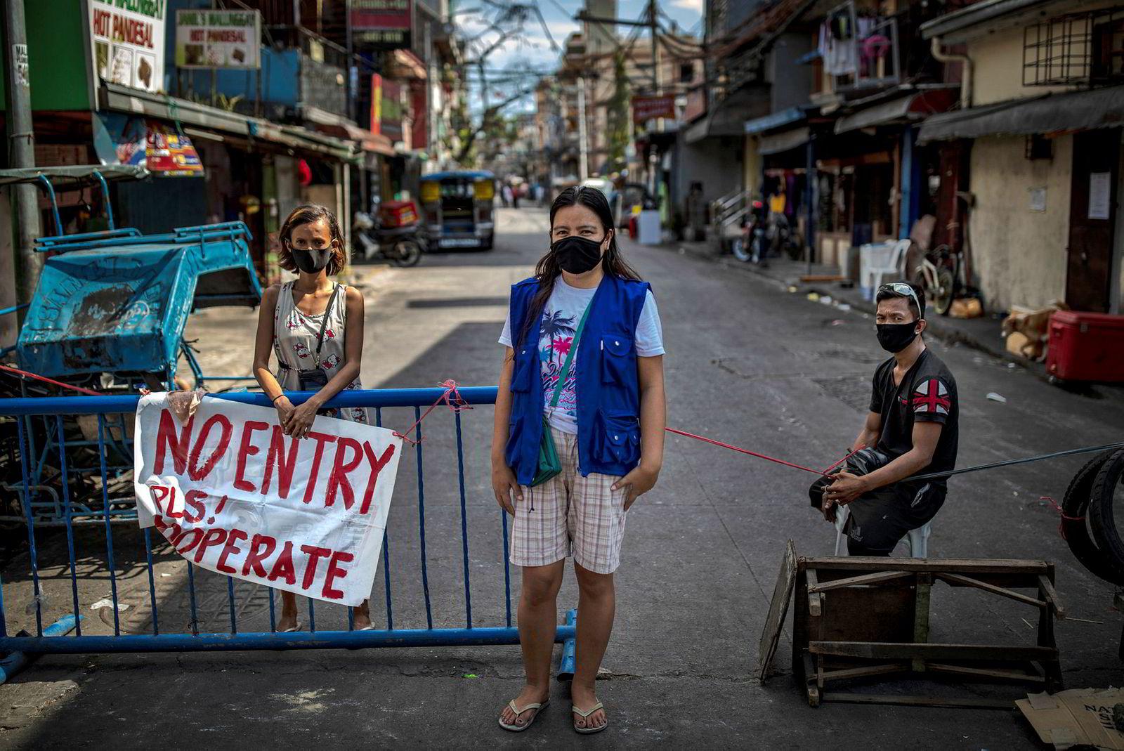 Snow Topacio, Karen Agustin og Jonathan Topacio vokter en provisorisk barrikade i Manila på Filippinene. Målet er å begrense trafikken i de trangeste smugene og gatene, i håp om å stoppe spredningen av koronaviruset.
