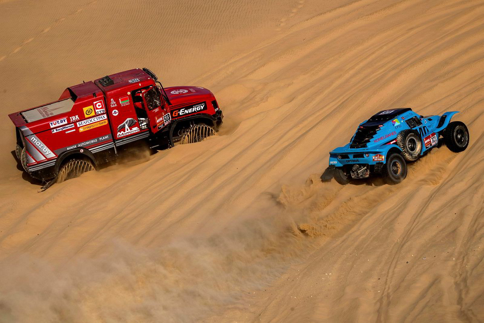 Sjåfør Dominique Housieaux fra Frankrike passerer Siarhei Viazovich fra Hviterussland som har satt seg fast i sanden på den 8.etappen av Rally Dakar.