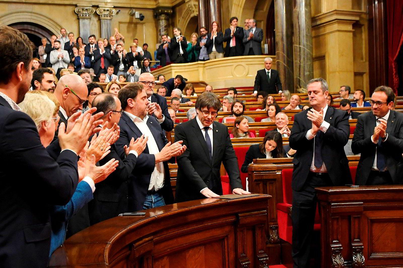 Presidenten for myndighetene i Catalonia, Carles Puigdemont, mottok applaus da han talte i regionsparlamentet tirsdag. Han aksepterte folkets mandat, men utsatte uavhengighetserklæringen for å få til en dialog med de nasjonale myndighetene.