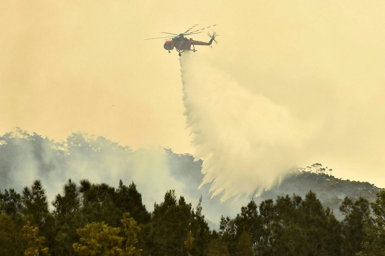 Slukkearbeidet foregår både på bakken og i luften. Her slipper et helikopter vann over brannherjede Batemans Bay i New South Wales.