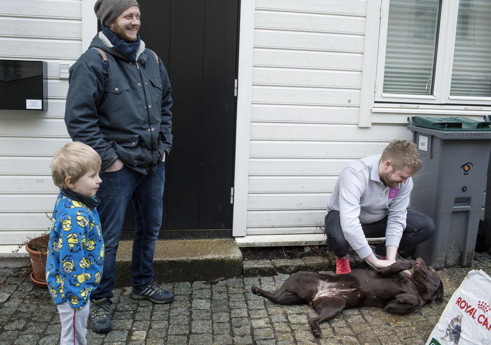 Erik Høsteland Åland (til høyre) hilser på labradoren Leia mens eier Hallvar Helleseth og sønnen Martin (5) ser på.