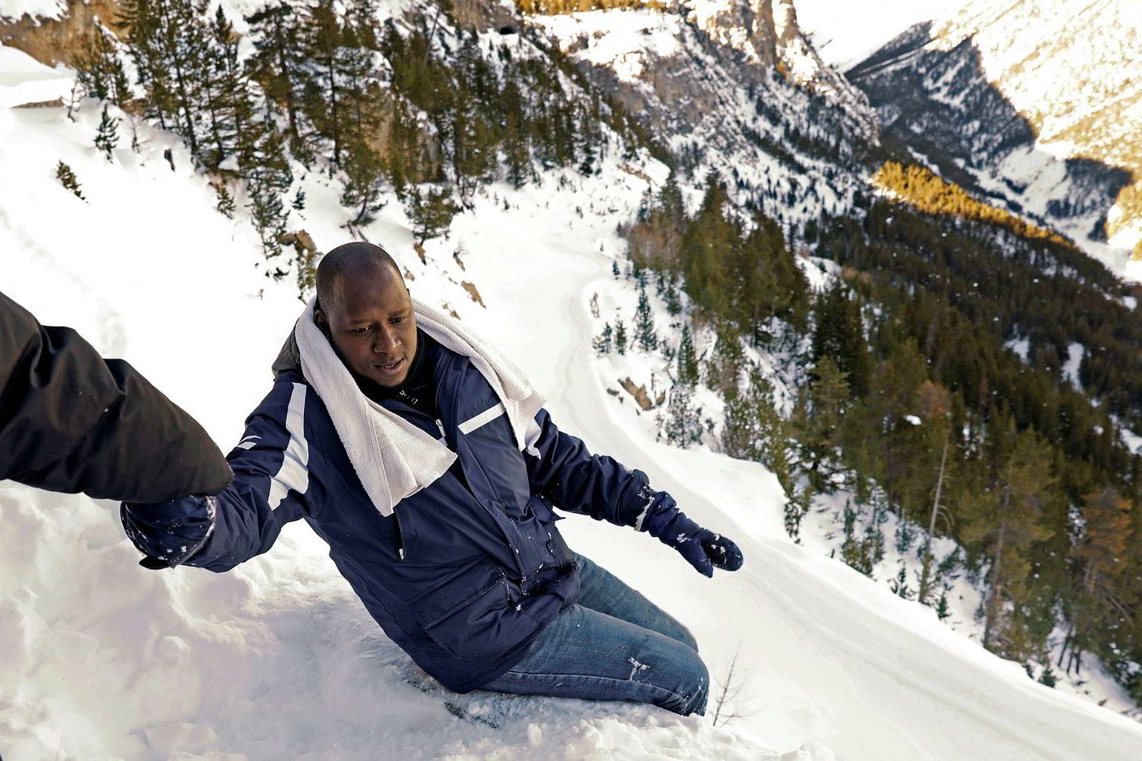 Abdullhai (38 fra Guinea får hjelp av en venn på ferden sin over Alpene fra Italia til Frankrike i nærheten av byen Bardonecchia i Nord-Italia. Bildet er tatt 21. desember.