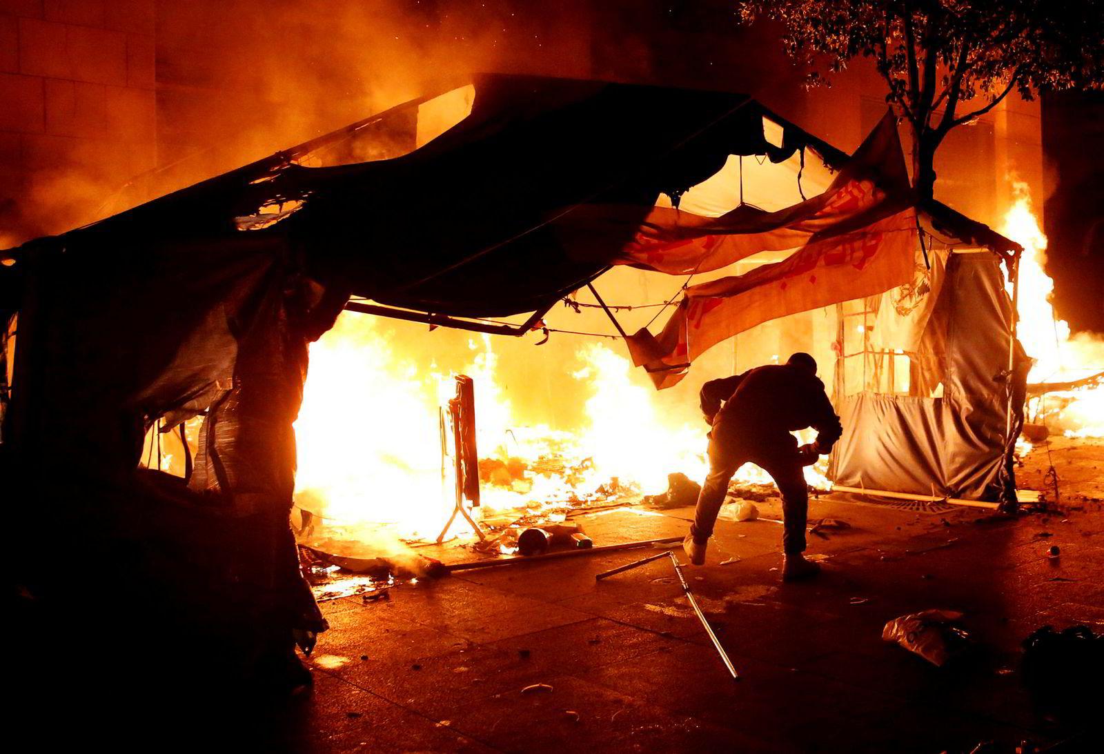 Mye ble satt fyr på i den libanesiske hovedstaden i helgen. Her forsøker en av de protesterende  å slokke et telt demonstrantene hadde satt opp. I tillegg til det lokale politiet ble også soldater satt inn for å stoppe urolighetene.