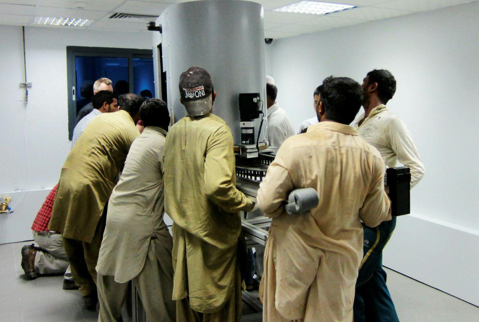 I 2012 bestemte RS Systems å flytte selskapets laboratorium fra Dammam til Abu Dhabi. Her hjelper noen lokale menn med å bære et av selskapets kjerneanalysesystemer.