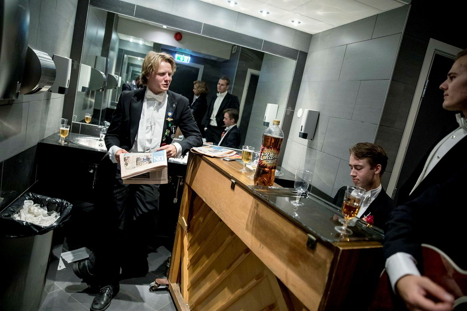 Mens immatrikuleringen fant sted i auditoriet ned gangen, sto Sverre Skjauff, Hans-Jørgen Jøssund og Kristoffer Stokke fra Det sanitære selskab for champagnebrus, næringslivsaviser og taffelmusikk på do.