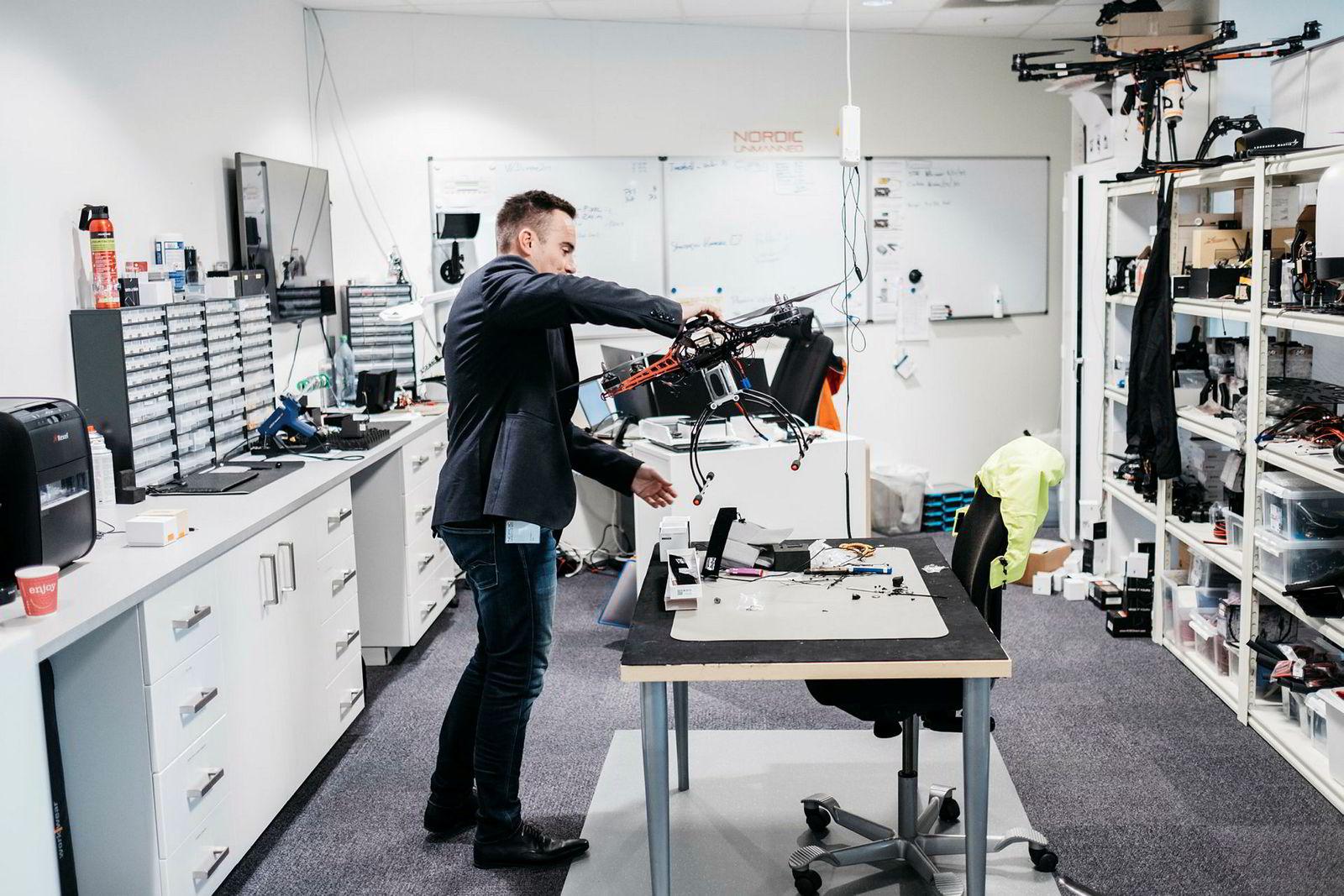 Daglig leder Knut Roar Wiig i Nordic Unmanned løfter en drone over på arbeidsbenken i verkstedet. Selskapet har vunnet en kjempekontrakt med EU og skal fly droner for å måle avgasser på skip.