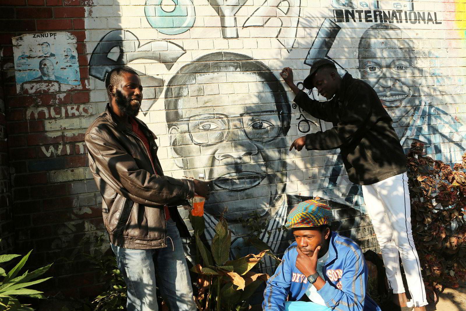 Tilhengere av president Robert Mugabe ved et veggmaleri av den tidligere presidenten i Zimbabwes hovedstad Harare.