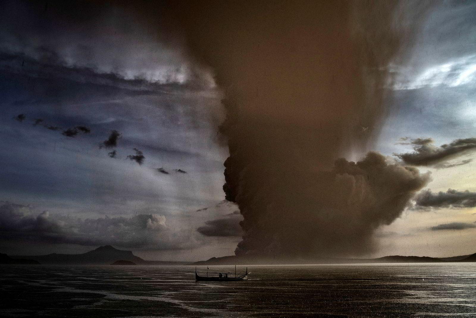 En fiskebåt seiler på sjøen, i bakgrunn vulkanen Taal.