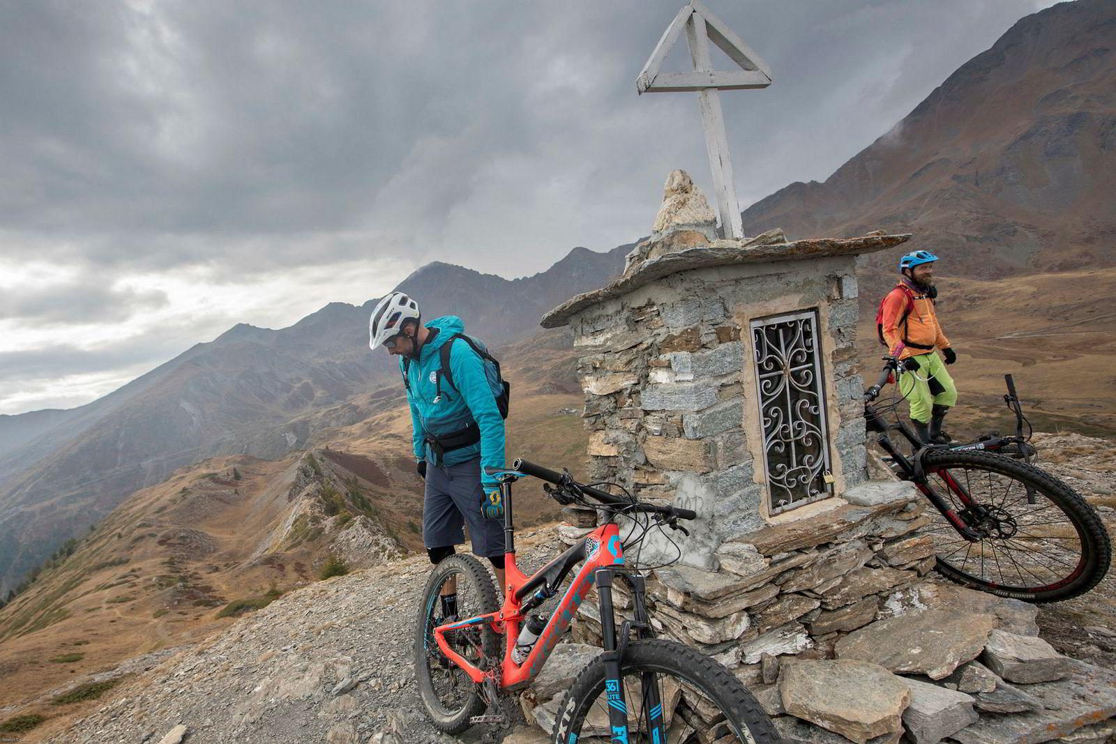 Før dagens siste sykkeltur hviler sykkelguide Fabrizio Charruaz og Bjørn Jarle Kvande beina på toppen av en fjelltopp .