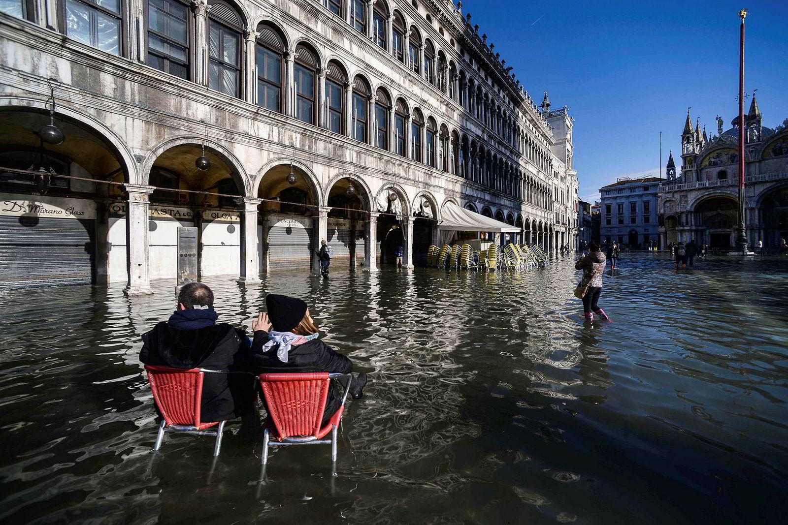 Turister sitter på restaurangstoler midt på den oversvømte Markusplassen.