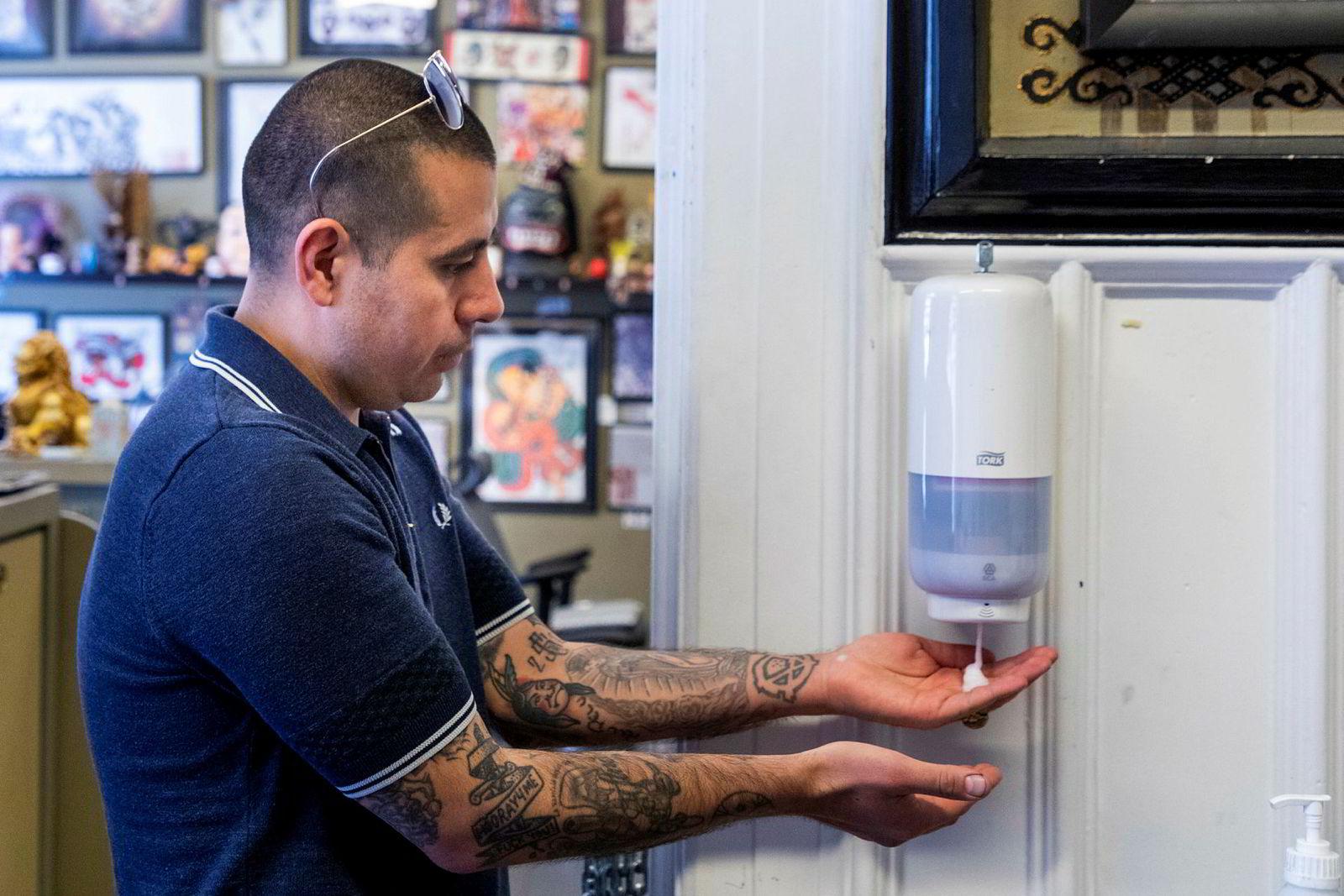 Dinson Purcell understreker at det første de nye kundene må gjøre er å desinfisere hendene ved hjelp av denne automaten.
