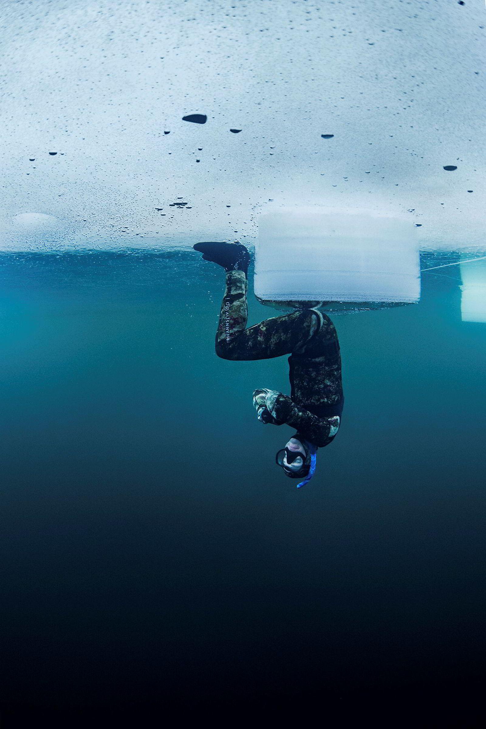 Helge Løvskar sitter på en isblokk under isen og teller sekunder. Fridykking under isen krever ro og total kontroll.