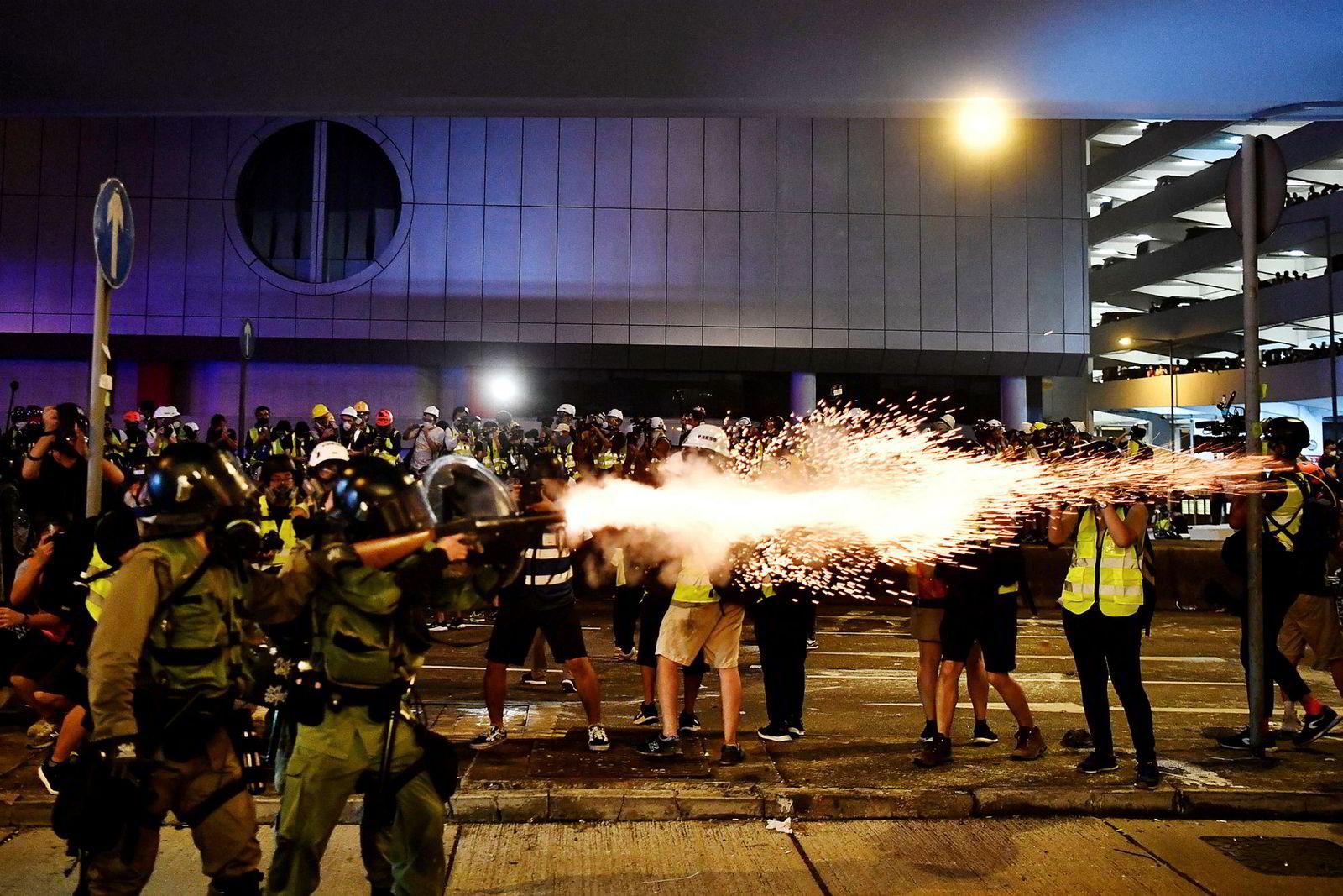 En politimann skyter tåregassgranat mot demonstrantene for å spre de etter en demonstrasjon.