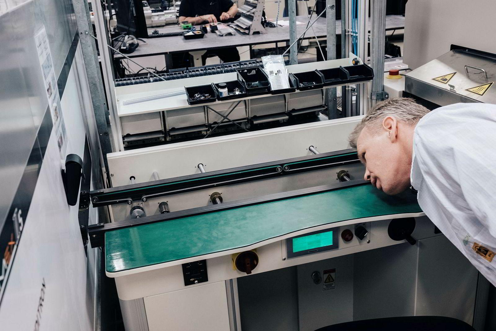 Zaptec-sjef Anders Thingbø er på besøk hos Westcontrol på Tau i Rogaland for å inspisere produksjonen av elbil-laderne til bedriften. Her venter han på at et kretskort skal komme ut av maskinen. Maskinoperatør Jan Roger Watland i bakgrunnen.