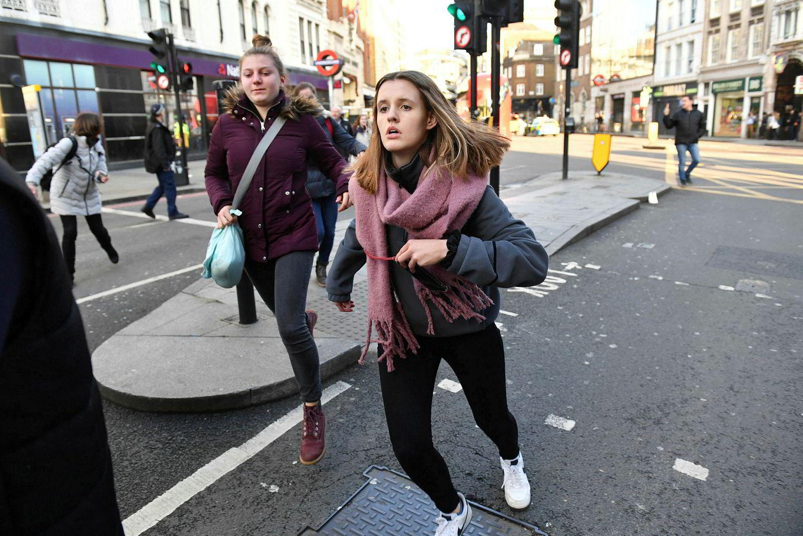 To kvinner avbildet mens de løper fra området.