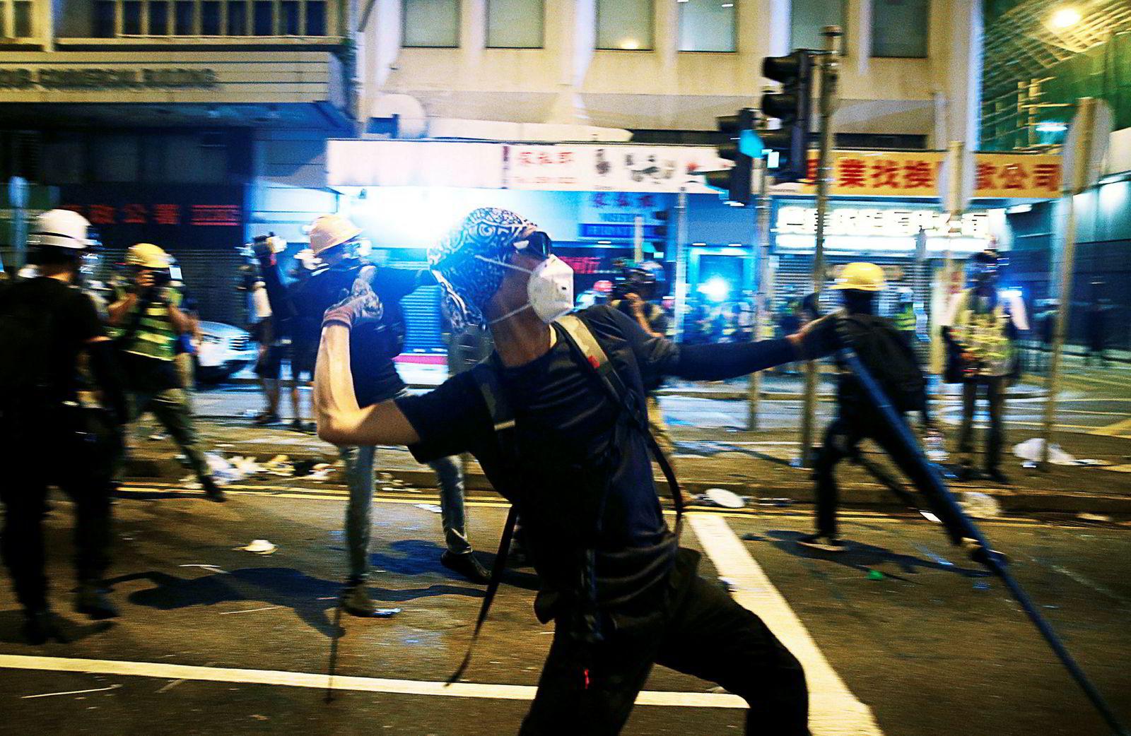 Anti-utleverings demonstranter kaster stein, etter en demonstrasjon for demokratiske reformer i Hong Kong.