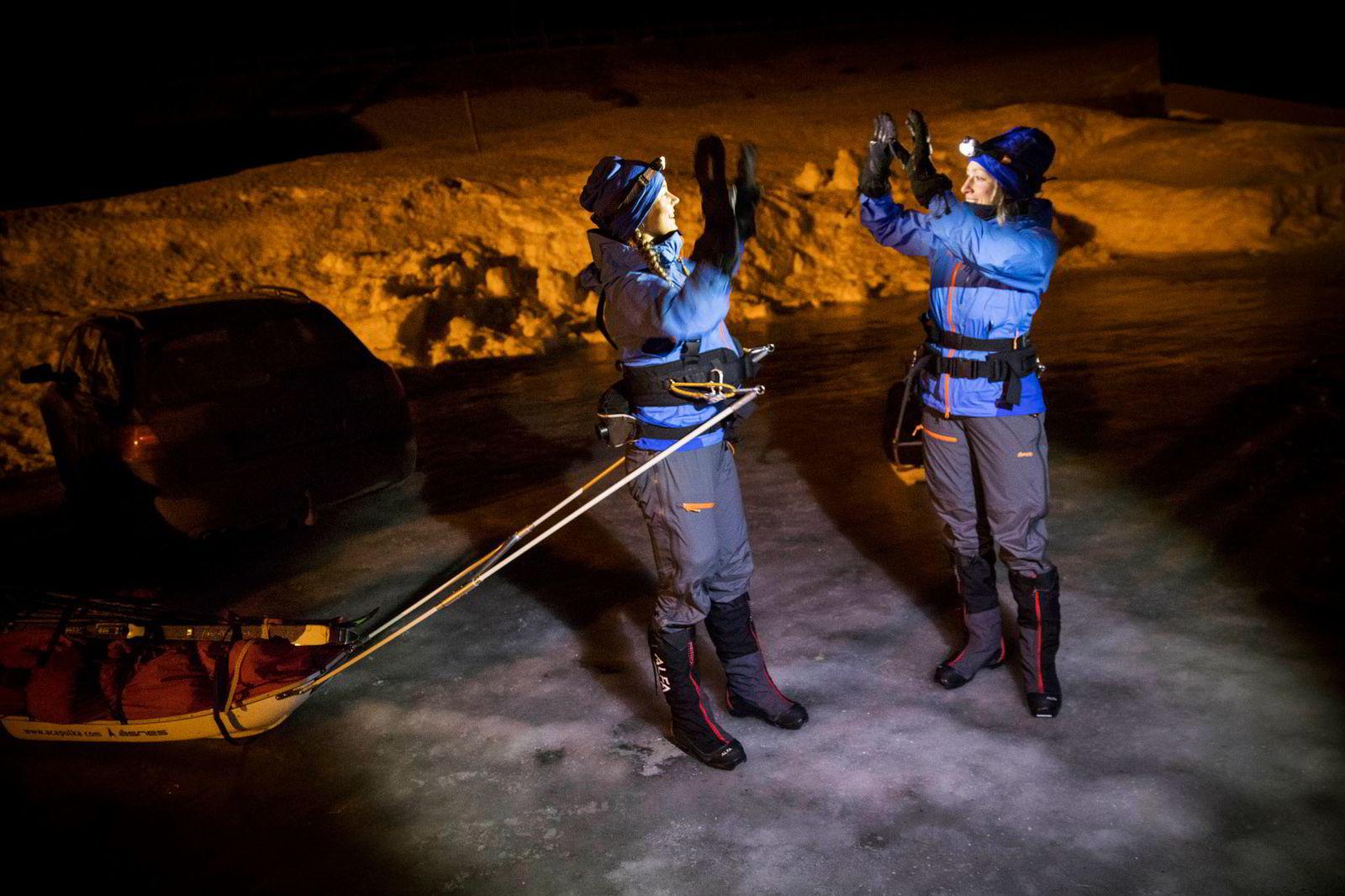 Ingeborg Kristine Lind, til venstre, og Line Sogn Plassen er klare til å gå ut fra Haukelifjell litt over midnatt og tar en high five. De to ligger i hardtrening før de skal gå Expedition Amundsen over Hardangervidda.