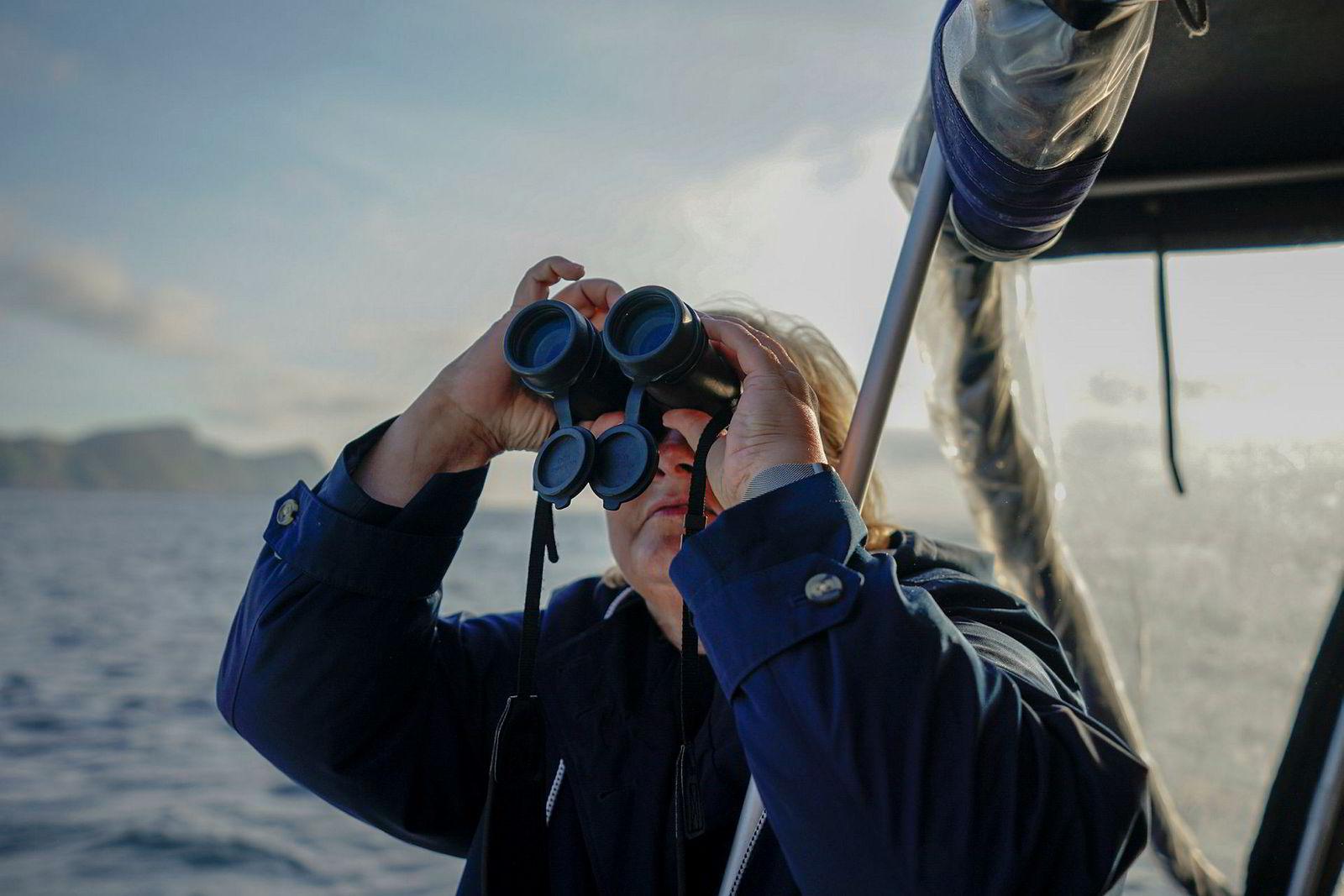 Statsminister Erna Solberg bruker en kikkert for å se på fuglefjellet på Runde. Mange av fuglene har bygget reder av plast