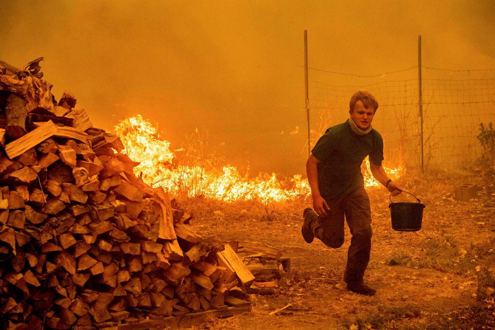 Alex Schenk bærer en bøtte med vann mens han kjemper mot flammene fra Ranch-brannen som er i ferd med å sluke huset hans nær Clearlake Oaks i California. Ranch-brannen er den ene av to branner som utgjør Mendocino-komplekset, den største skogbrannen i Californias historie.