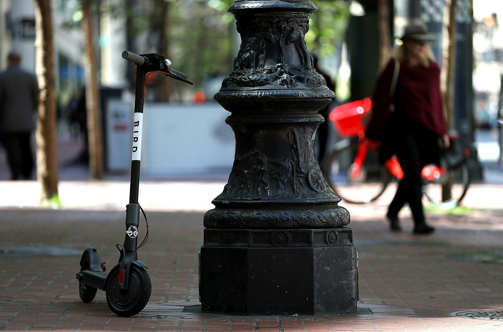 En sparkesykkel fra Bird står parkert ved en lyktestolpe i San Francisco. Syklene kan parkeres hvor som helst, noe som kan skape litt trøbbel i bybildet.