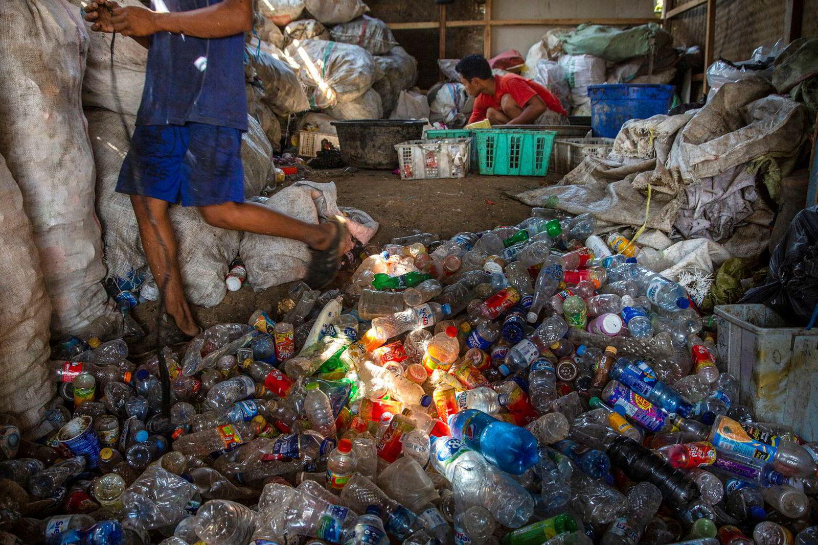 En mann sorterer plastavfall som han senere vil selge. Alt er hentet opp fra Citarum, verdens mest forurensede elv, ifølge Verdensbanken.