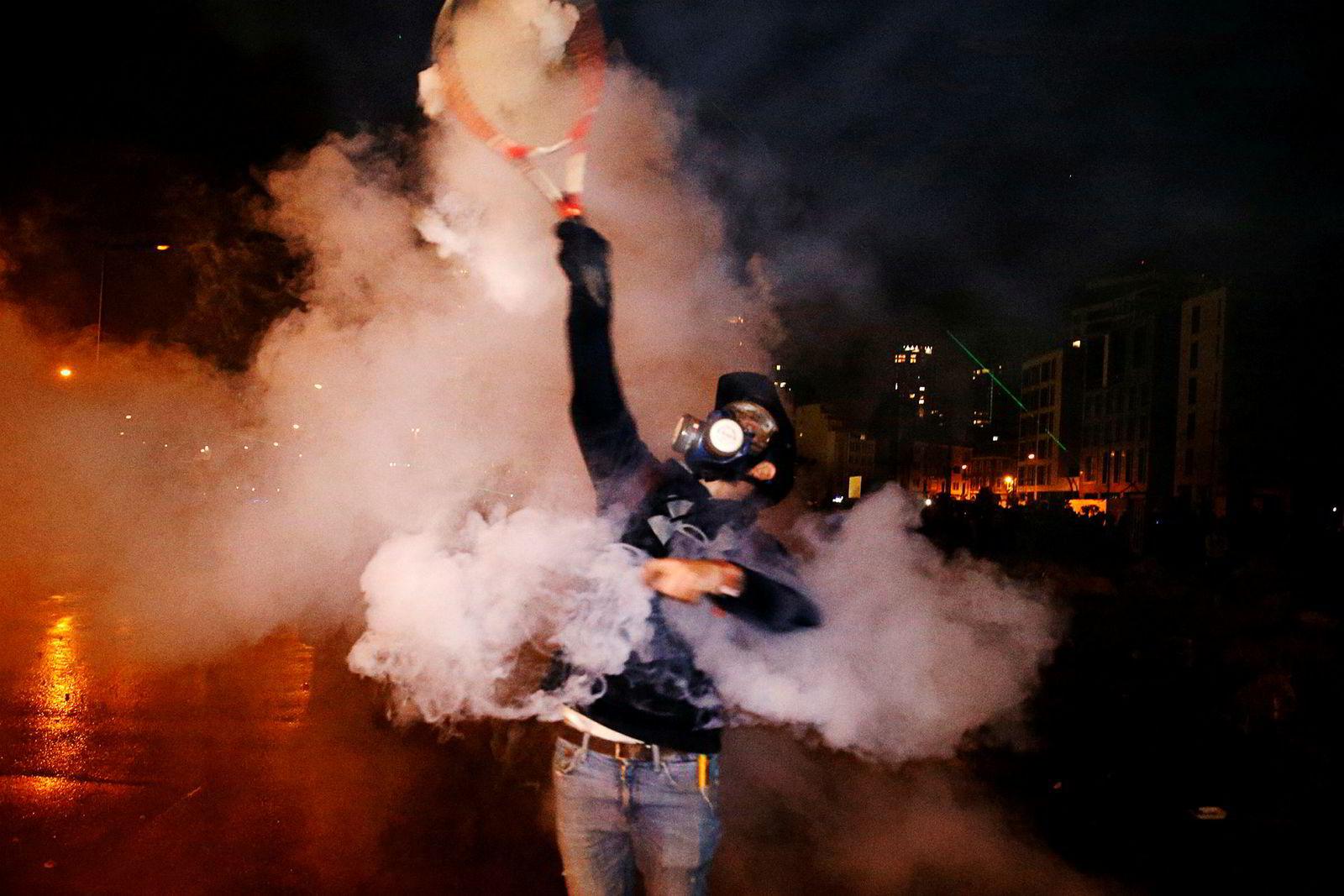 En demonstrant forsøker å slå tilbake politiets tåregassgranter med en tennisrekkert nær parlamentet i Beirut.