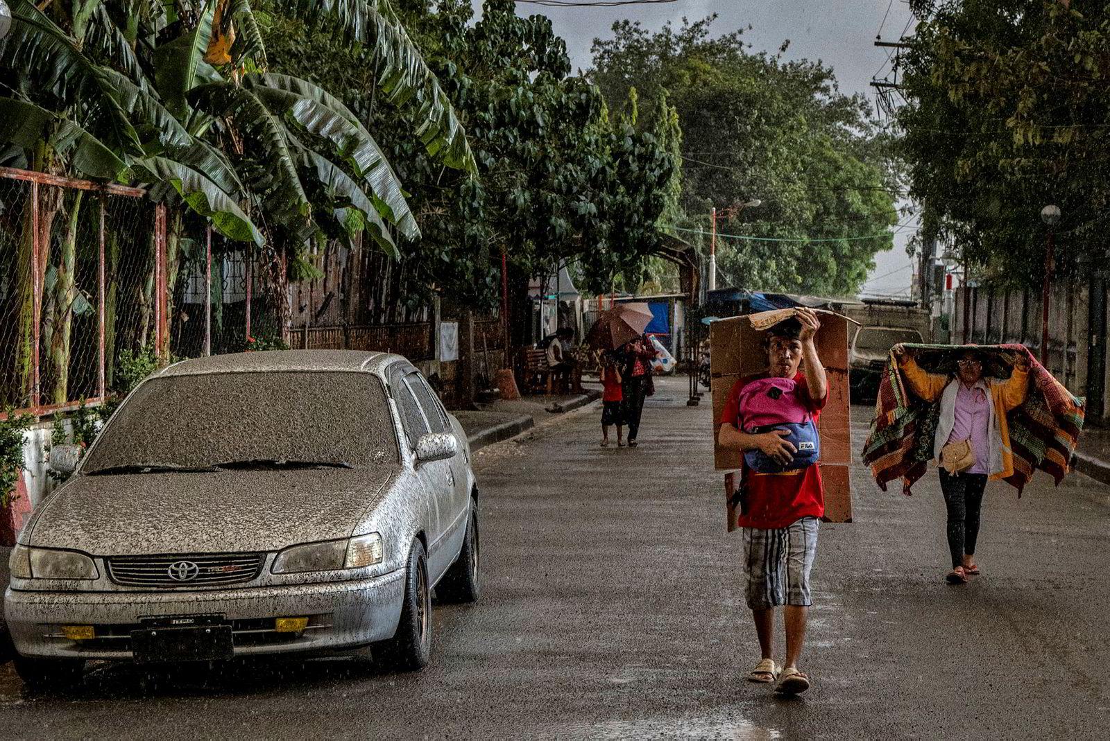 Innbyggere som går langs veien prøver å beskytte seg selv mot aske og rein.