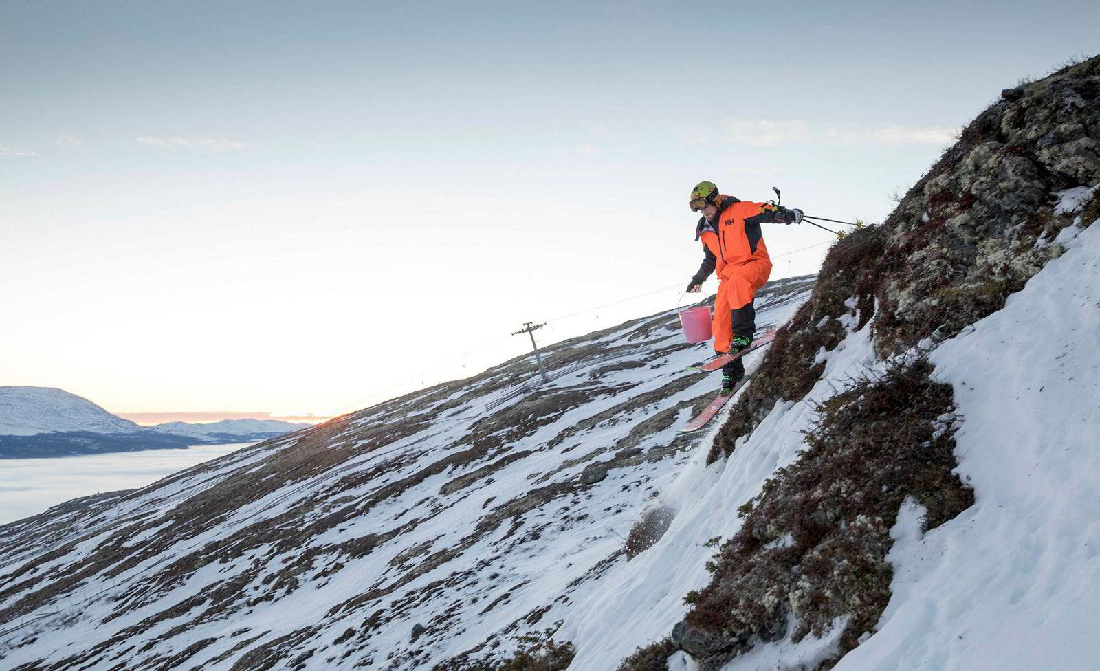 Dennis Risvoll kjører ned klippen han senere skal hoppe fra med en bøtte salt i den ene hånden. Han salter tilløp og landingssted i et forsøk på å gjøre det litt mykere.