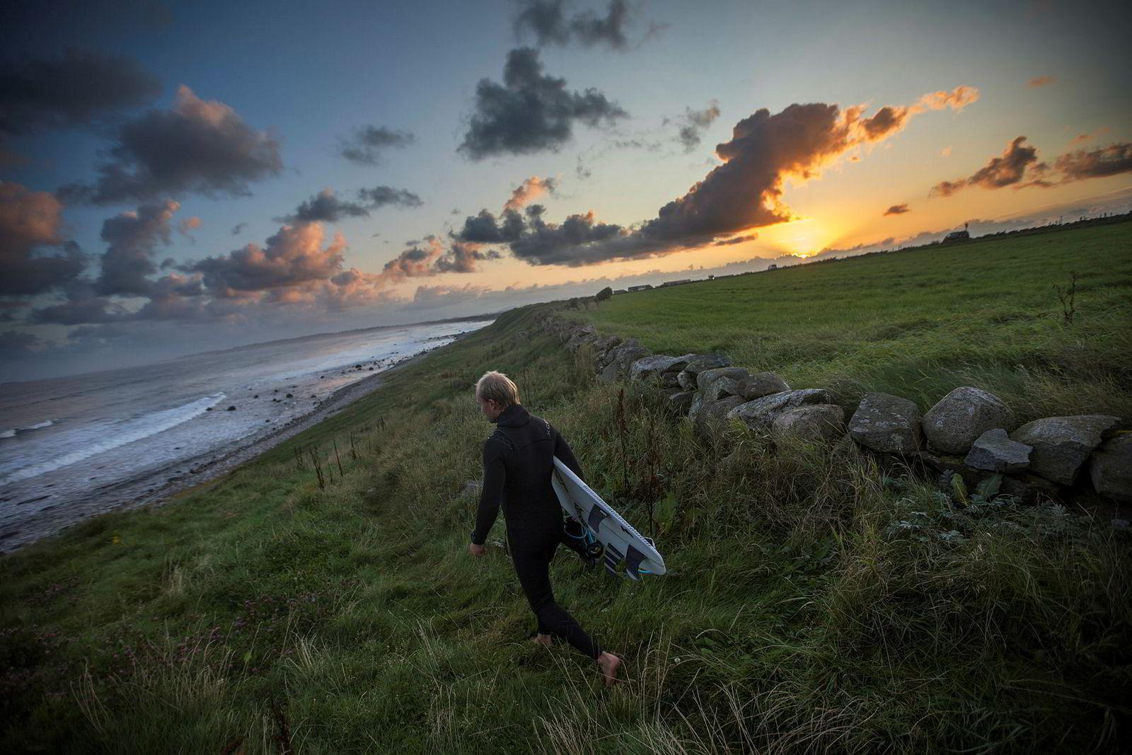 Sturla Fagerhaug står opp med solen for å komme seg tidlig i vannet med surfebrettet.