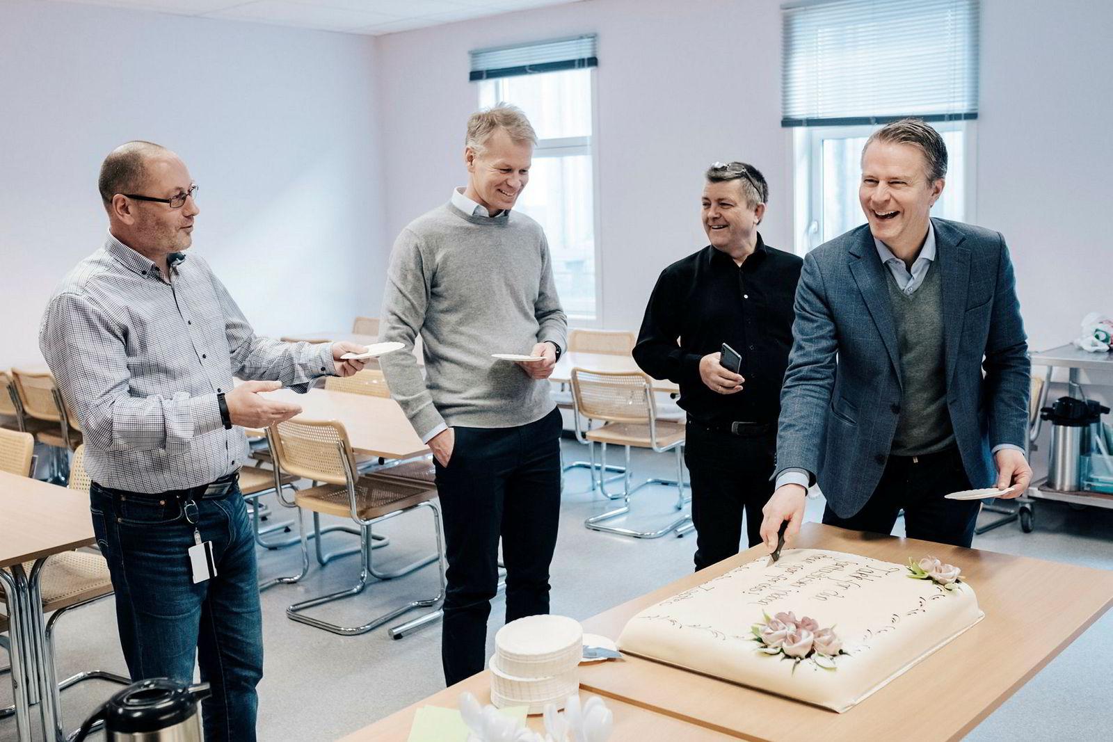 Westcontrol-sjef Leif Petter Skaar (til venstre) tar imot marsipankake fra Zaptec-styreleder Pål Selboe Valseth (til høyre) for å markere at 10.000 ladere er produsert. I midten står Zaptec-sjef Anders Thingbø og hovedeier Lars Helge Helvig (i svart).