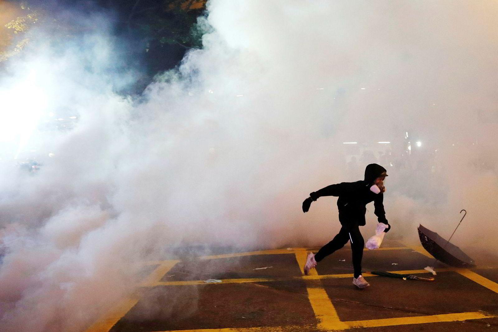 En demonstrant løper vekk fra tåregassen.