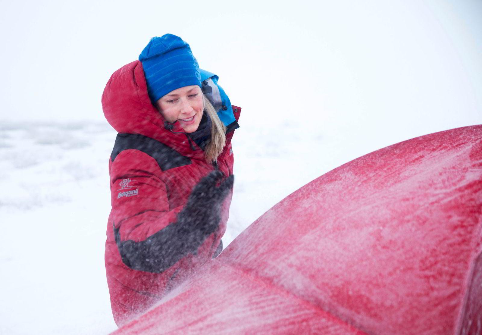 Line Sogn Plassen banker rim av teltet før det pakkes ned.
