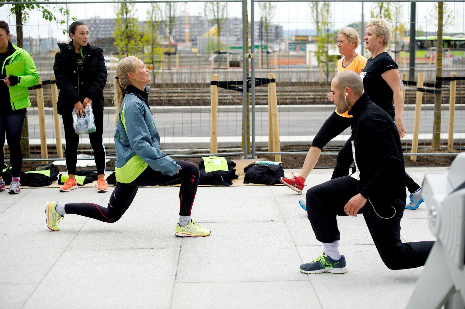OPPVARMING: Personlig trener ved Elixia, Hedvig Bang (til venstre) ledet oppvarmingen, som var høyst nødvendig denne kalde maidagen i Bjørvika. FOTO: Mikalela Berg